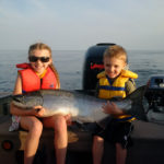 Hannah, 9, and Colton Primrose, 5, holding a giant salmon on Lake Ontario.