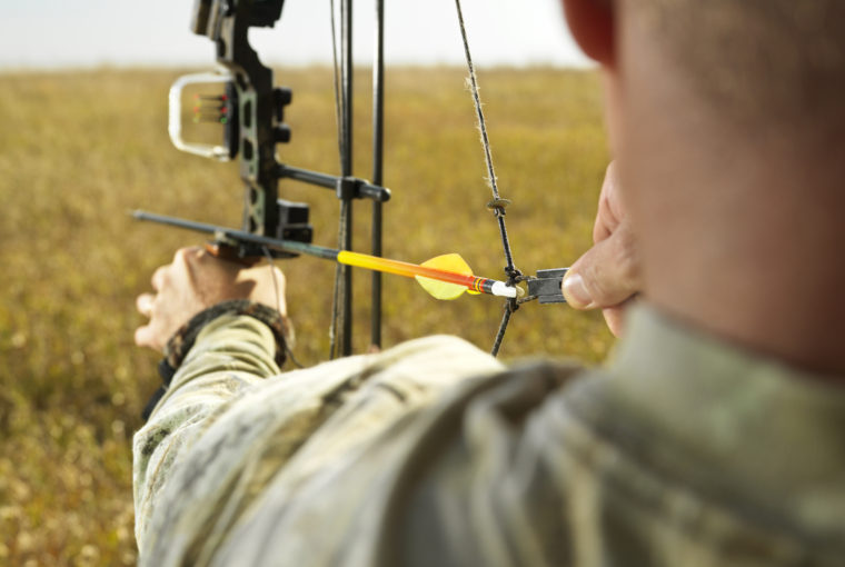 spooking deer - bowstring maintenance - Bow hunter in field pulling back arrow on compund bow.