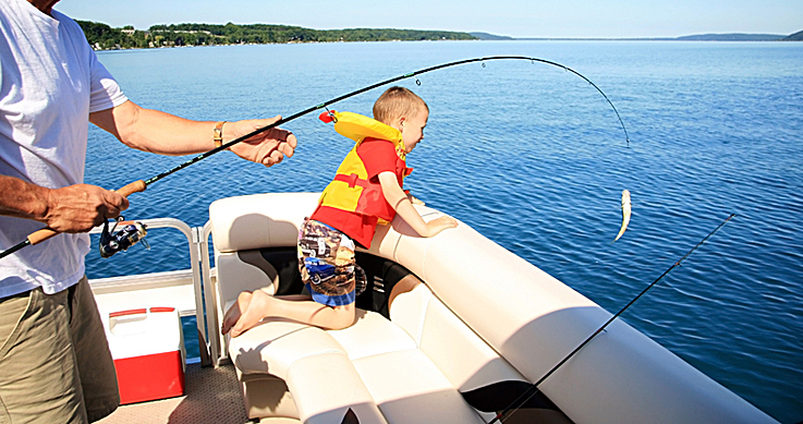 family fishing week - child in a boat with parent fishing