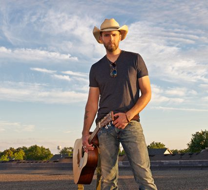 Dean Brody stands forlornly with a guitar in a field