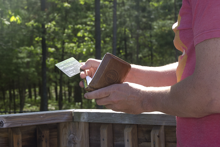 a person pulls out an old hunting licence from their wallet