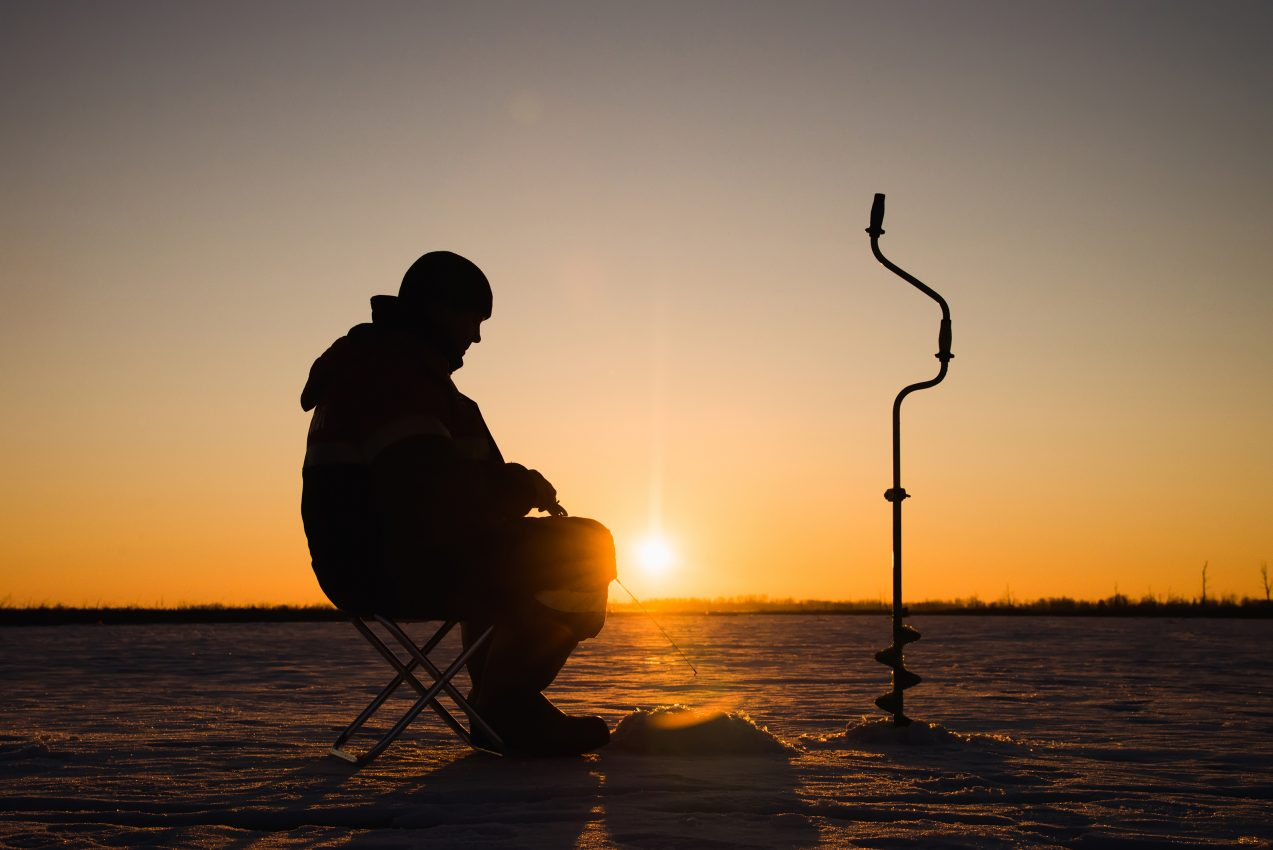 Silhouette of a fisherman in winter ice fishing at sunset