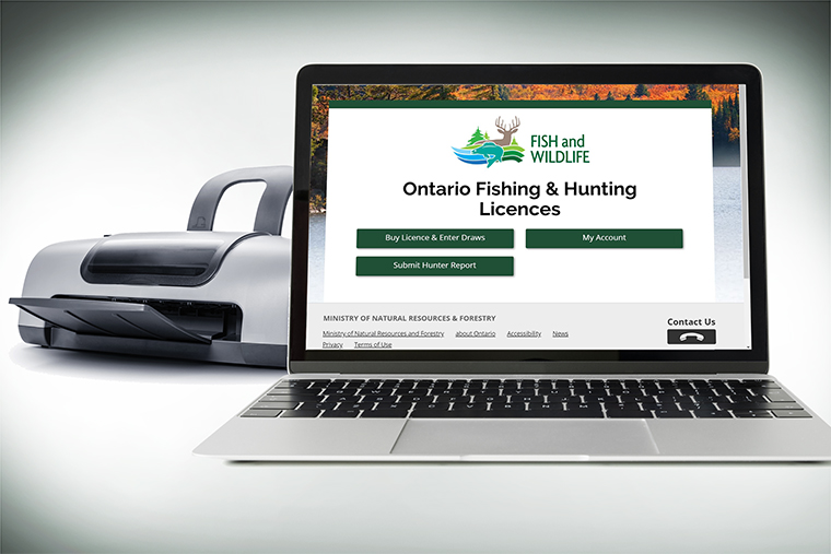 Image of a laptop on the Fish and Wildlife service website, with a printer in the background