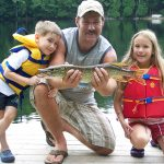 Dean Young of Fort Erie displays a northern pike he caught with children Brett and Karisa Young.