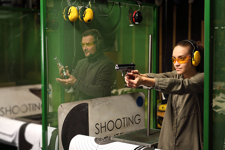 A woman and man at a shooting range practicing their aim.