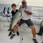 Sean Kanellis, 9, displays a catch while enjoying a day on Lake Ontario with Ontario OUT of DOORS national sales director Stephen Bates, as well as his brother Connor and captain Vito Dattomo of Lord of the Kings King Salmon Charters (not pictured).