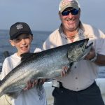 Connor Kanellis, 10, displays a catch while enjoying a day on Lake Ontario with captain Vito Dattomo of Lord of the Kings King Salmon Charters, as well as his brother Sean and Ontario OUT of DOORS national sales director Stephen Bates (not pictured).