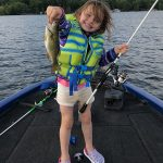 Kara Liscombe of Coboconk holds up a smallmouth bass while fishing with her dad.