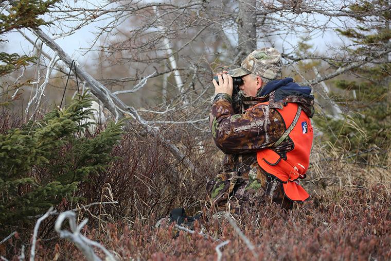 hunter peering through binoculars