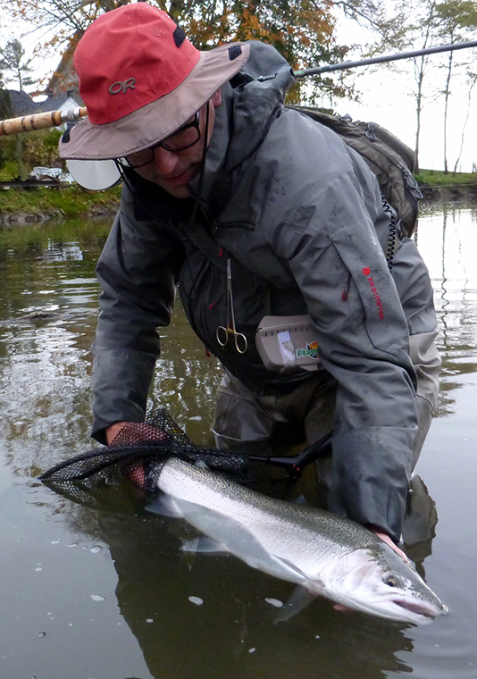 angler holding rainbow trout in river