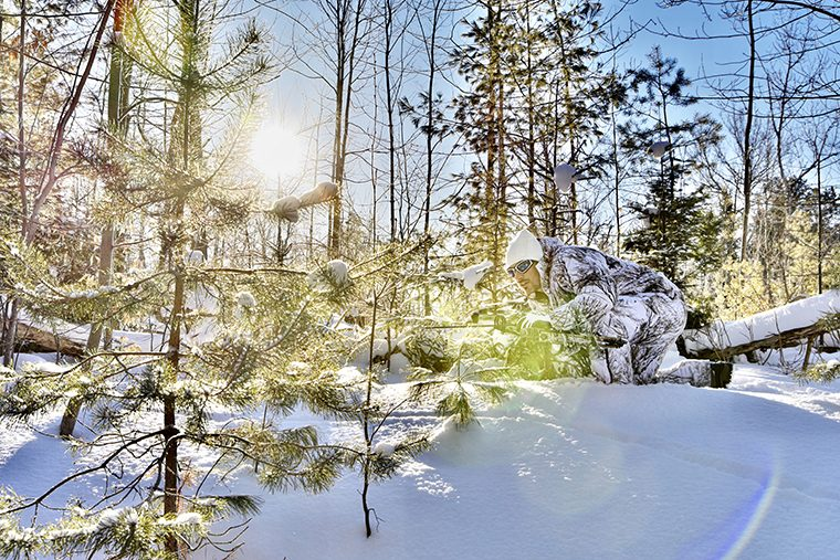 camo-clad hunter stalking deer in snowy forest
