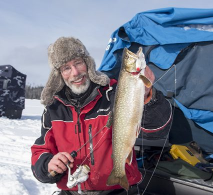 angler holding trout while ice fishing