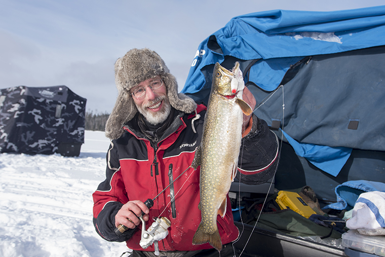 man holding trout while ice fishing