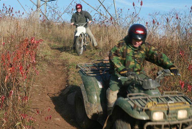men riding ATV and dirt bike down a hill