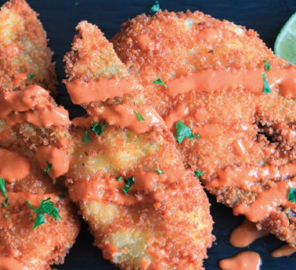 some breaded and friend walleye cheeks in a welcoming drizzle of buffalo sauce
