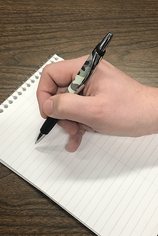 A hand holding a camo patterned pen on a pad of paper, poised.