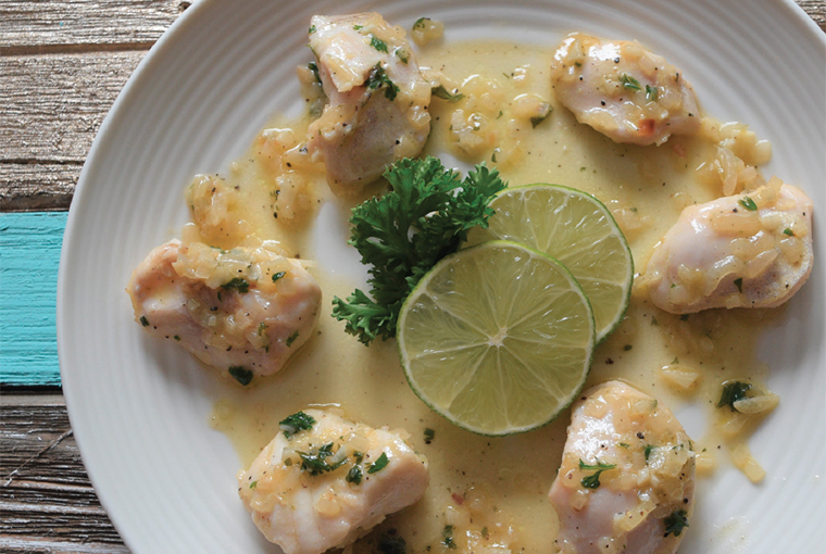 fish cheeks arranged on a plate decorously with sauce and garnish