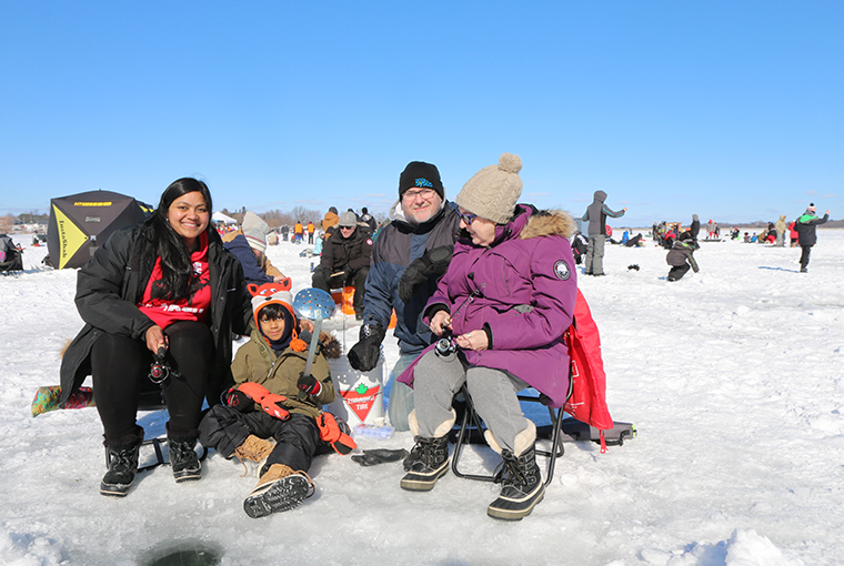 a group of people squatting in front of an ice fishing hole