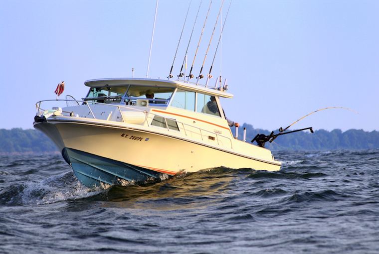a boat with fishing lines roars through the water