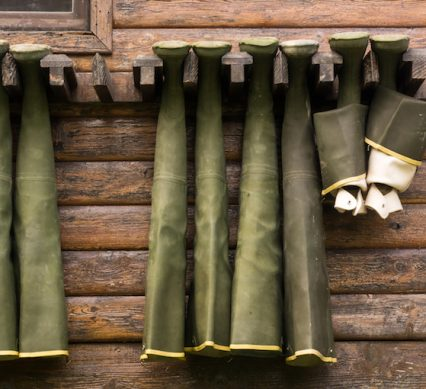 hanging rubber hip waders in green