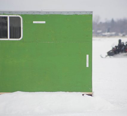 a green ice hut on a lake