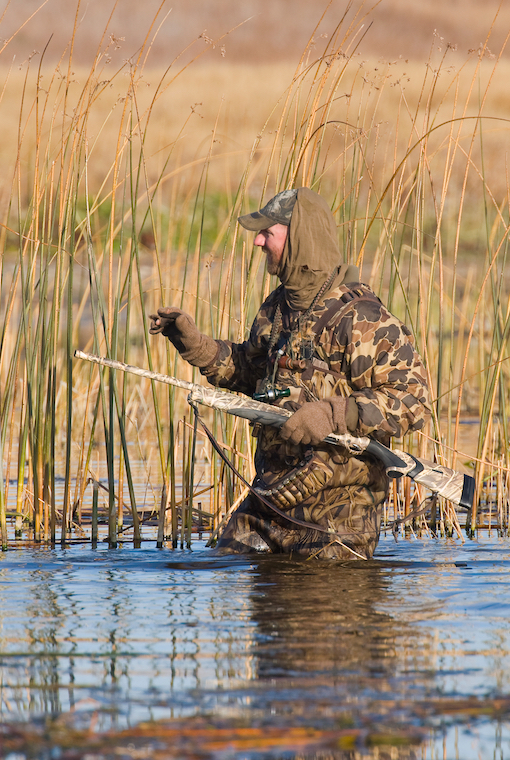 More waterfowl changes as a duck hunter wades through water, gleefully, in camouflage.