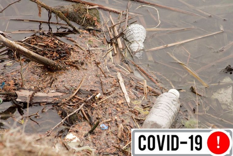 a muddy waterbody with littered bottles