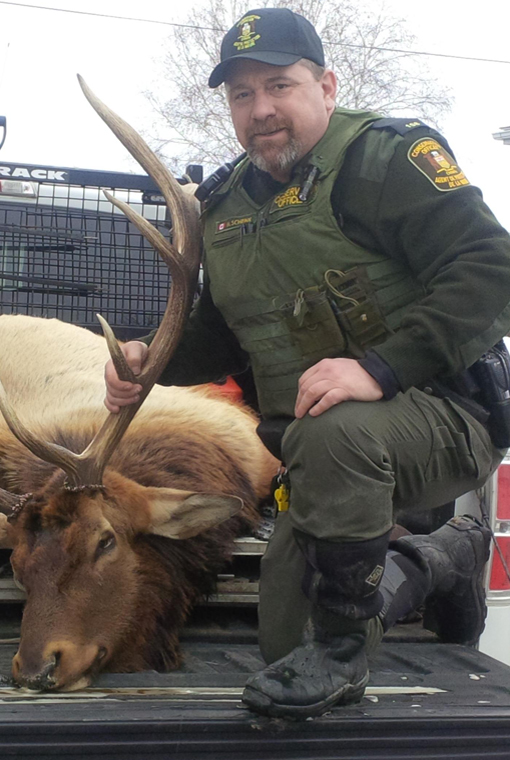 Mike Schenk named CO of the year poses with harvested cervid