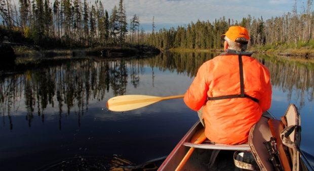 a blaze orange hunter paddles on a quiet lake