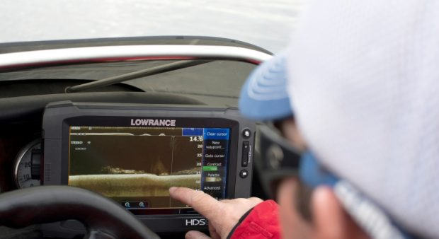 Person pointing at a fish finder screen