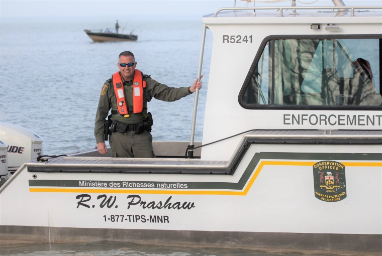 A Conservation Officer standing on a boat
