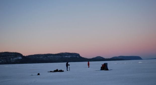 Anglers' silhouettes on the ice