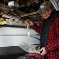 Man holding tangled fishing line and lured in his garage