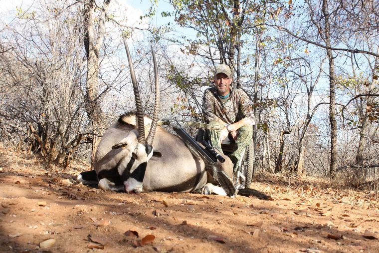 a man sits next to a felled African oryx