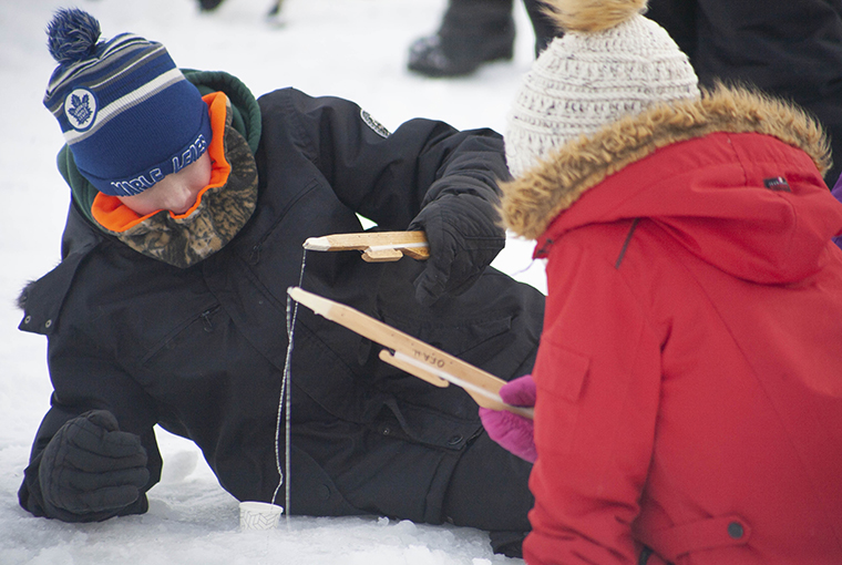 Children ice fishing with jigging sticks