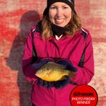 Photo Friday winner, Jason Barnucz of Delhi, submitted this photo of his wife Heather. She loves fishing, but isn't always able to join the party. She caught this awesome pumpkinseed — a sunfish on a sunny day!