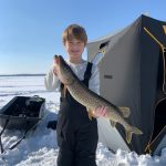 Max Moreau of Waubaushene, 7, holds his first pike caught while ice fishing on Georgian Bay with his father, Ryan Moreau.