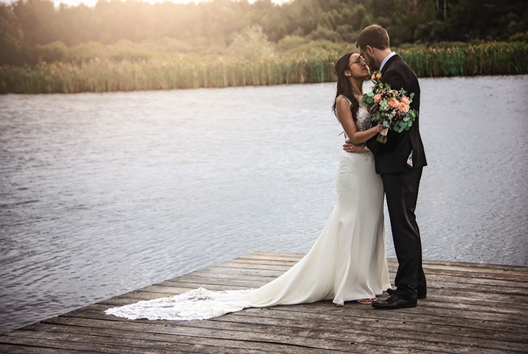 Just-married couple standing on a dock at Royal Ashburn