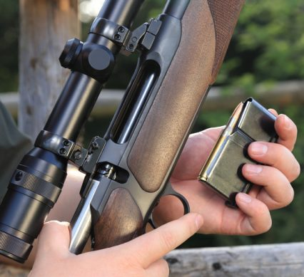 A Hunter loading his hunting rifle gun with magazine