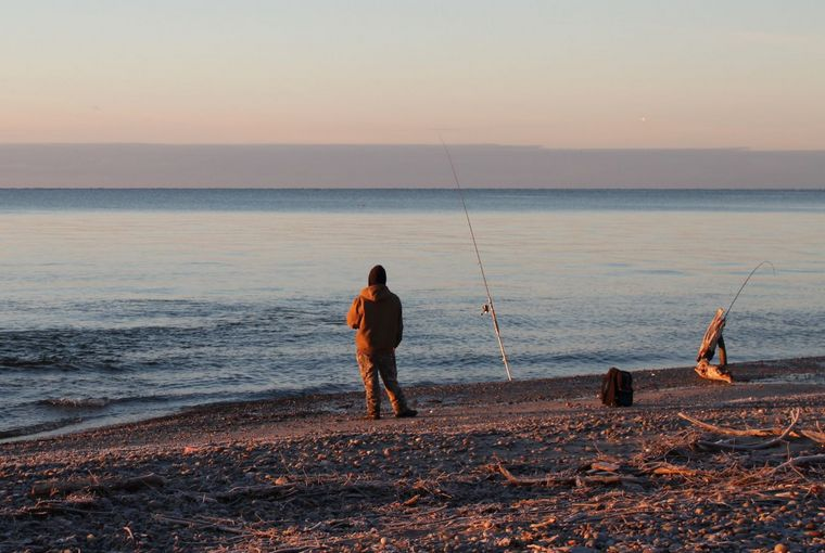 An angler fishing the frog waters at the mouth of a Lake Ontario tributary