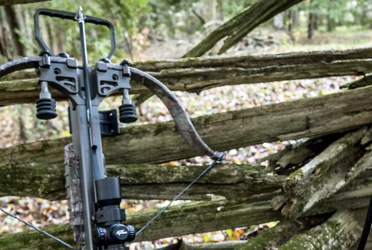 crossbow on a cedar rail fence