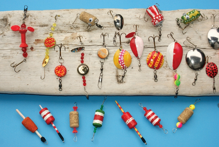 Various homemade fishing lures displayed on a piece of drift wood.