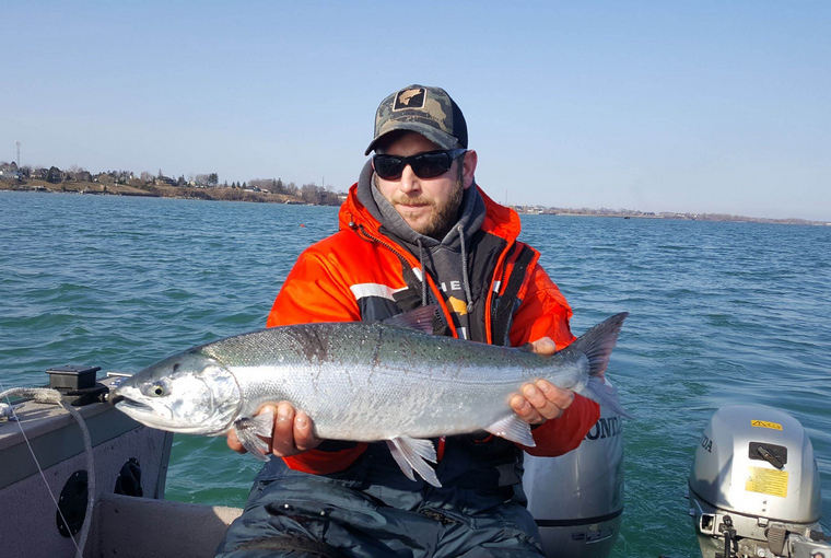 Angler holding coho while sitting in a boat.