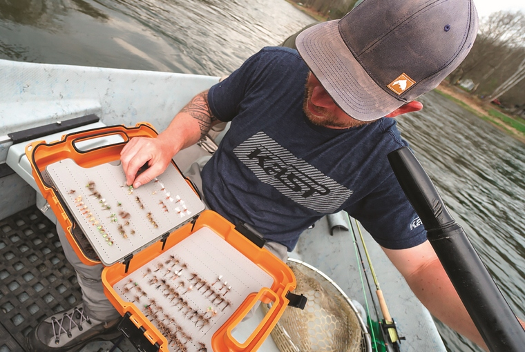 Angler sits in a boat with an opened case of trout flies to select from.