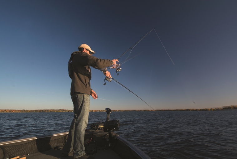 An angler standing on the bow of his boat casting into the water.