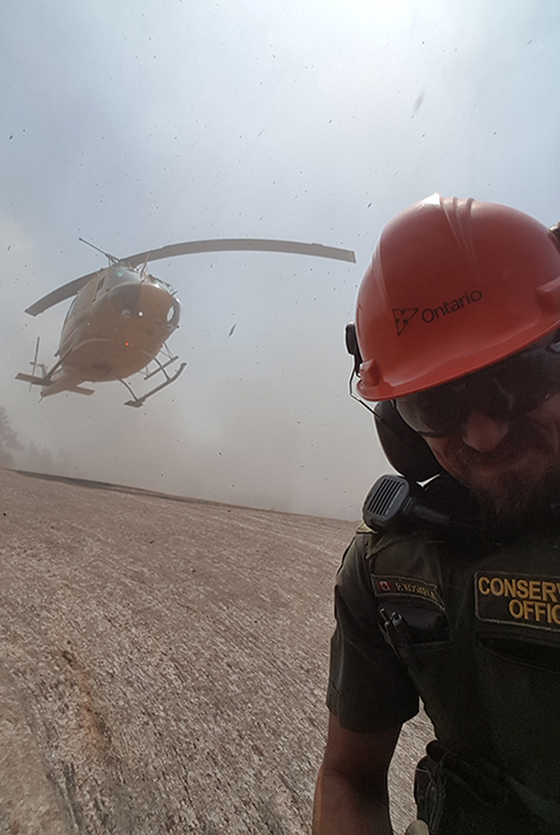 CO Peter Koskela taking a selfie near a helicopter