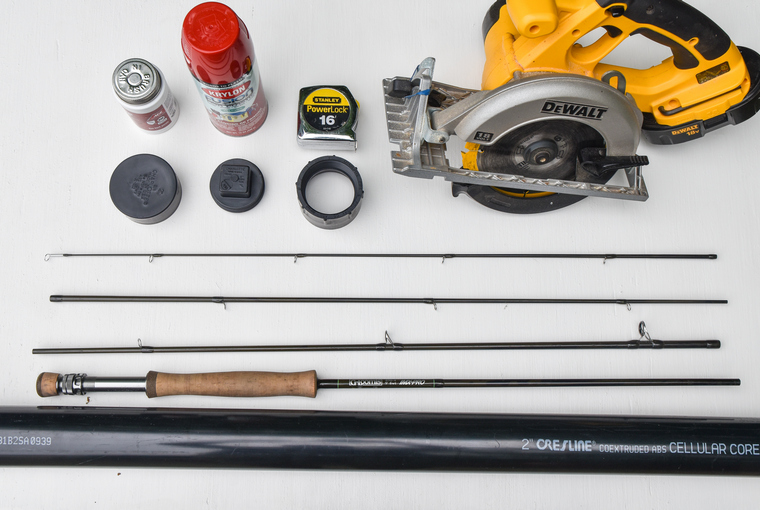 Circular saw, APBS pipe and end caps, four piece fishing rod, measuring tape, spray paint, ABS glue laid out in preparation for assembly.