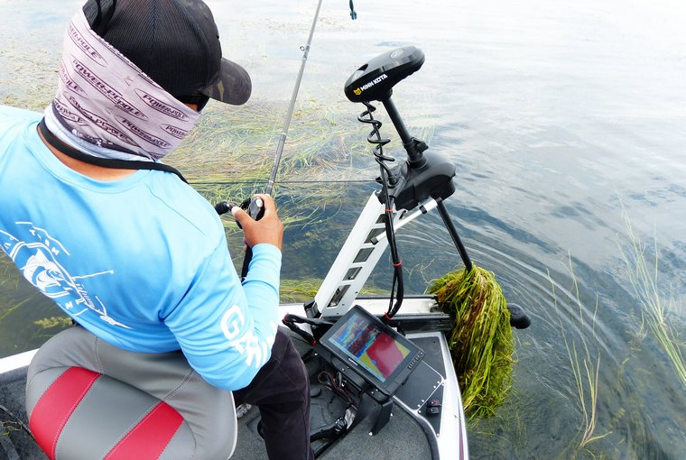 Angler stands on the bow of his boat looking at his trilling motor covered in weeds.