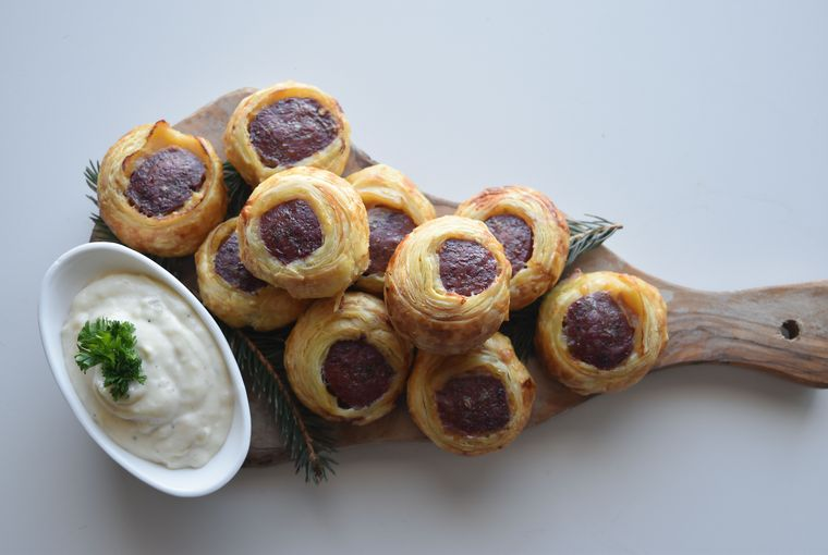 Bear sausage bites wrapped in golden brown puff pastry served with a dip on a wooden cutting board.