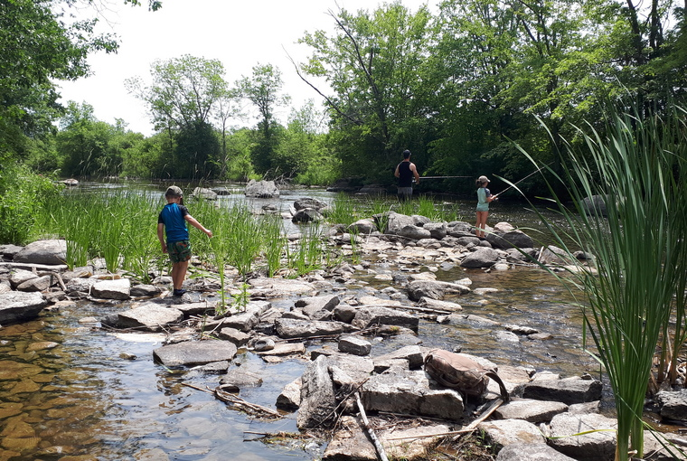 Family fishing on the bank of a rocky river bank